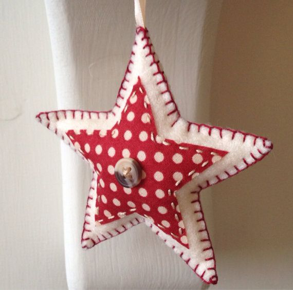 These star-shaped Christmas decorations are handmade to order. Made from wool felt, each of the three ornaments are decorated with a different complementary fabric and finished with a reclaimed button and blanket stitch edging.    Whether hung from the tree or around the house, or even given as a wee stocking filler - these charming decorations are sure to add to the joy this coming yuletide.    As these are made to order, please allow up to two weeks for delivery within the UK, or up to 4…
