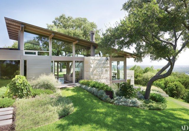 Set atop a steep incline overlooking downtown Austin, Texas, Hillside House, a two-level home designed by Lake | Flato Architects, uses floor-to-ceiling windows to accentuate the breathtaking view.