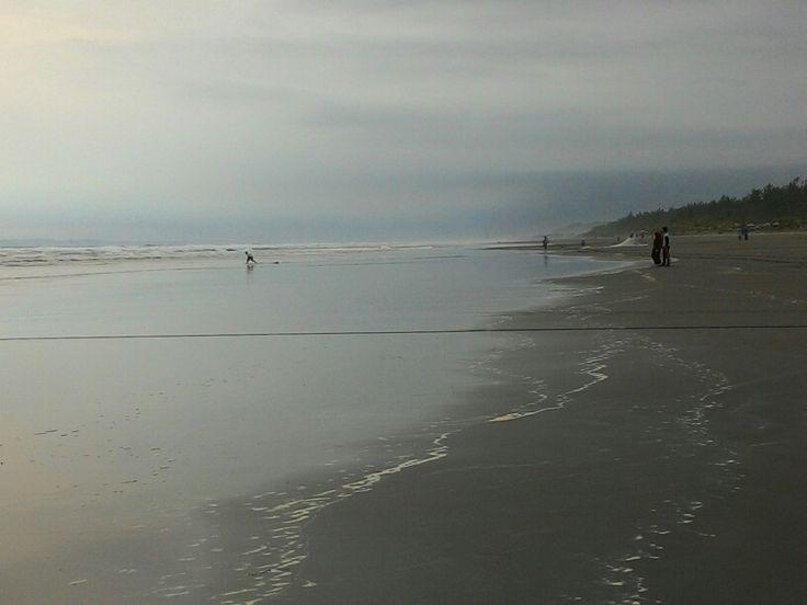 Pencari ikan tebar jala di pinggir pantai