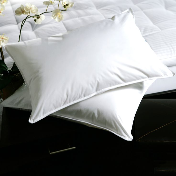 Sleep in comfort with these soft goose feather pillows. Each one features a hypoallergenic blend of goose feathers and down, with a plush layer of down alternative. This set of two bed pillows will cradle your head in a perfect medium density.