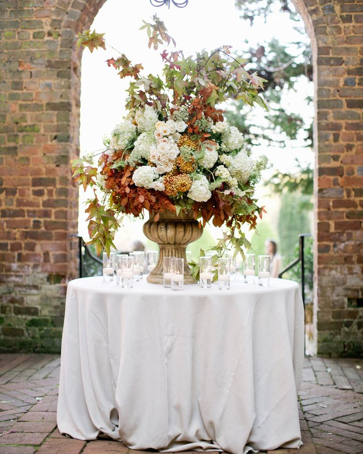 A stately urn filled with maple vine, white hydrangea, autumnal chrysanthemum, majolica spray roses, and Dutch Queen Anne's lace marked the entrance to the ceremony.