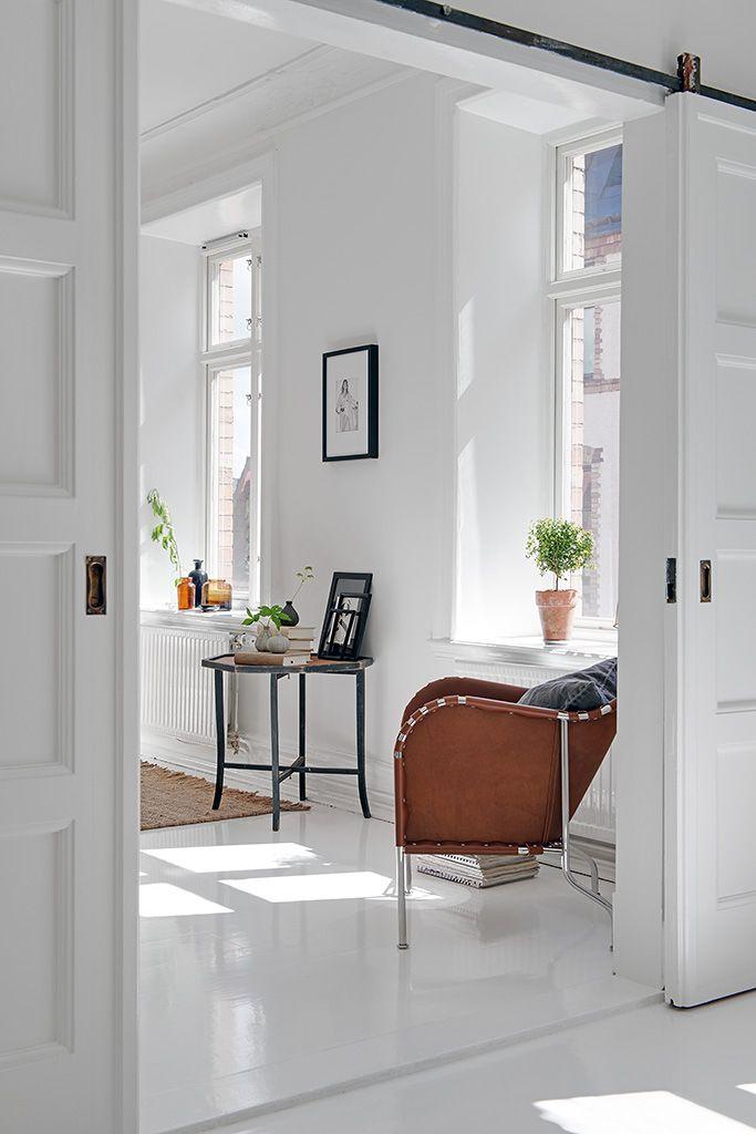 De grote ramen zorgen voor genoeg zonlicht en warmte. Twee traditionele houten deuren geven toegang tot een werkkamer waar het vrolijke en zachte behang een speelse afwisseling is naast de moderne witte basis.