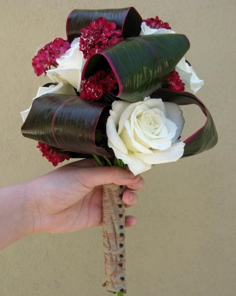 Rolled ti leaves with white roses and burgundy scabiosa