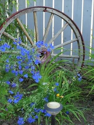 I Love Old Wagon Wheels in the Garden Landscape... My Grandpa put a post in the ground and made it a merry go round even with seats!!!!