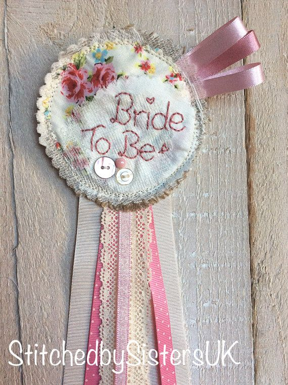 ideal for a classy hen party,  Beautiful handmade rosette badge especially for a special day personalised to your choice  A 10cm across circle of gorgeous vintage inspired layered fabrics and lace with button trim hand embroidered wording and ribbons making it 30cm long. available with mother of the bride and bridesmaid on as a package please ask for details.  these are made to order, in many different colour schemes 2nd picture was for a purple bride.  ** matching wands also available…