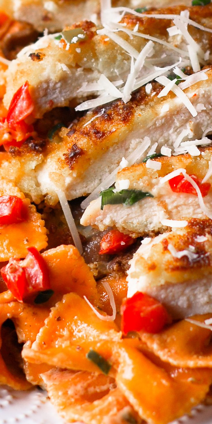 Louisiana Chicken Pasta - delicious Parmesan crusted chicken served over bow tie pasta with mushrooms, green onions, bell peppers and tomatoes in a spicy New Orleans sauce. Cheesecake Factory's copycat recipe. Southern food, recipe.