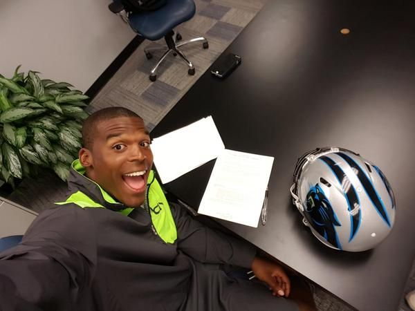 Cam Newton takes a selfie while signing contract extension