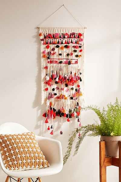 Fun boho-inspired wall hanging with allover pom detailing. Ready to hang with an attached string (hardware not included). Perfect on a wall or a near a window in any space!