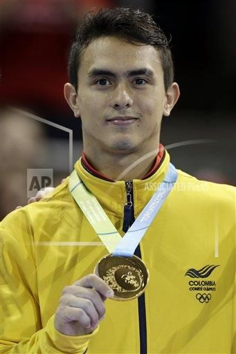 Colombia's Jossimar Calvo poses wearing his gold medal after winning it in artistic gymnastics parallel bars competition in the Pan Am Games in Toronto, Wednesday, July 15, 2015.
