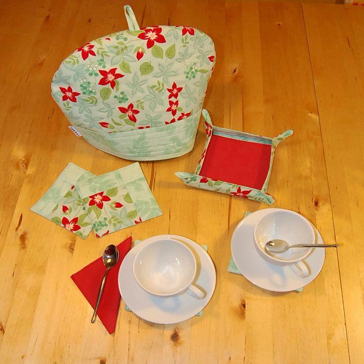 Juego de té, compuesto de cubre-tetera, bandejita y cuatro posa-tazas. Verde menta con flores rojas. Precio: 30 €