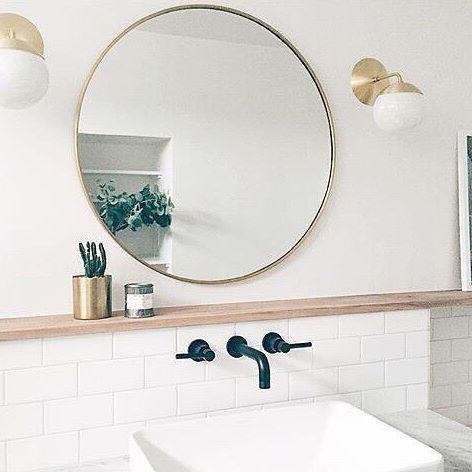 Round mirror with globe light sconces