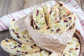 "Cranberry Pistachio Biscotti Recipe is one of the authentic biscuits originated from Italy. It also is known as ""Cattuccini"" as the name means it is twice baked in the oven. They are very crunchy and dry so usually, they are dipped in a hot drink and consumed. They are usually oblong shaped and resembles the rusk texture. But the only difference is that they are filled with nuts, dry fruits, and essence which give it an extra crunch to the cookie. Serve the Cranberry Pistachio Biscotti…"