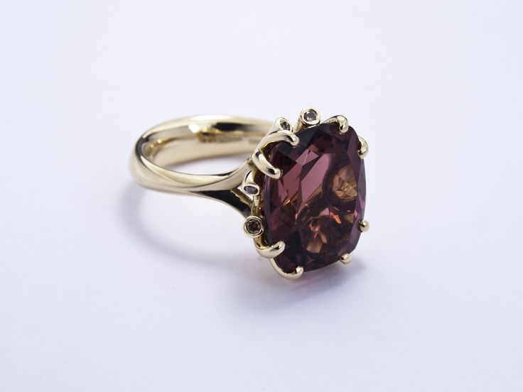 18ct red gold Meadow ring with plum tourmaline and copper diamonds Inspired by a summer pasture near Jon's home, with exquisite organic detailing, each piece is uniquely striking.The band nips in towards the shoulders, flowing and swirling up to the stone, where it splits to form tendrils; some becoming claws, others terminating in round brilliant cut diamonds that peek under the stone. #Fairtrade #Fairtradefortnight #JonDibben #Meadowring