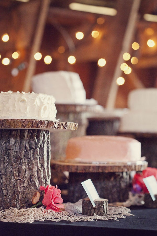 Log cake stands at rustic barn wedding