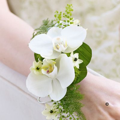 Rich in exquisite detail, this stunning wrist corsage is a beautiful style statement. Two exotic white orchids are complemented with perfect little ornithogalum flowers. Perfect for your prom, graduation or bridal party flowers | Booker Flowers & Gifts, Liverpool | Free Flower Delivery Liverpool