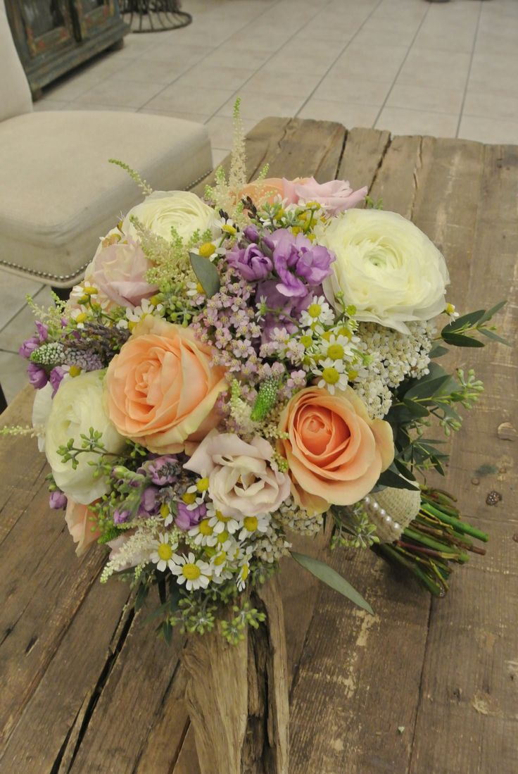Beautiful bridal bouquet with Roses, Ranunculus, Velonica, Astilbe, Yarrows, Phlox, Lisianthus, Tanacetum and Seeded Eucalyptus