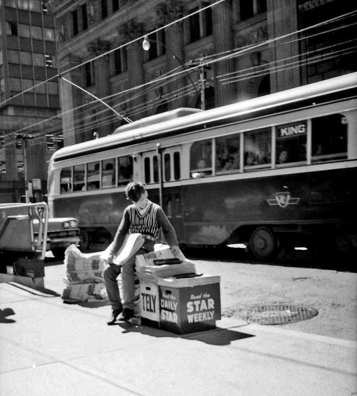 A paperboy on King St. W in Toronto, circa 1965. City of Toronto Archives photo.