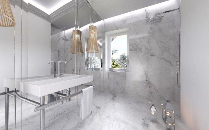 Aranżacja wnętrza łazienki w białym marmurze. Jasny kamień i fazowane lustra nadają lekkości niewielkiej łazience.