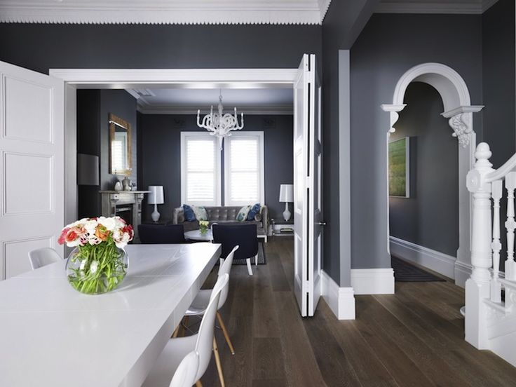 Dining room with dark gray walls paired with crisp white crown molding with millwork and glossy white folding doors leading to formal living room.
