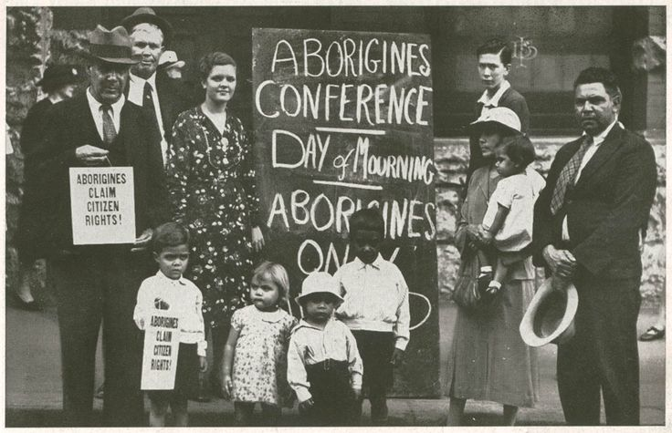 "Image 1.  A blackboard displayed outside the hall proclaims, ""Day of Mourning"". From the collections of the State Library of NSW."