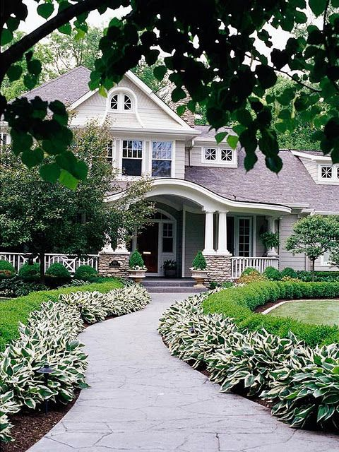 lovely house with curved walkway lined with hostas