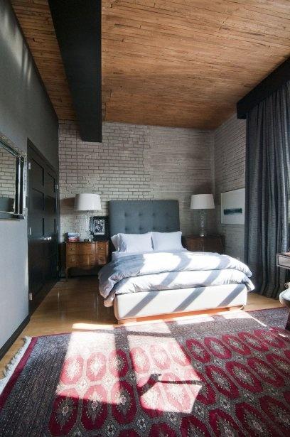 La chambre est aménagée sous un haut plafond en mill floor avec poutre et murs de briques apparentes. (Photo : Valérie Vézina, collaboration spéciale)