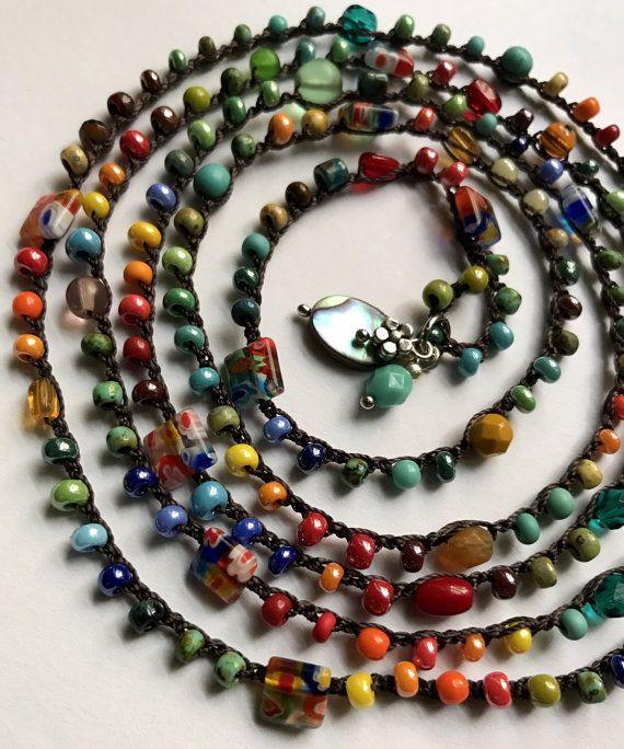 Divertente e colorato, perline uncinetto avvolgere braccialetto o una collana fatta di una bella miscela di perle molate di vetro ceco, perline e perle pressate di vetro nei toni delloro, giallo, rosso, verde acqua, aqua, turchese, ulivi, aranci, bronzo e tan alluncinetto sul filo crochet in nylon in marrone scuro. Accentati con naturale e fascino di perline di vetro e metallo.  Questo allegro pezzo misura circa 50(127 cm) e avvolge fino a 7 volte su un polso 6-6.5 ma può essere avvolto più…