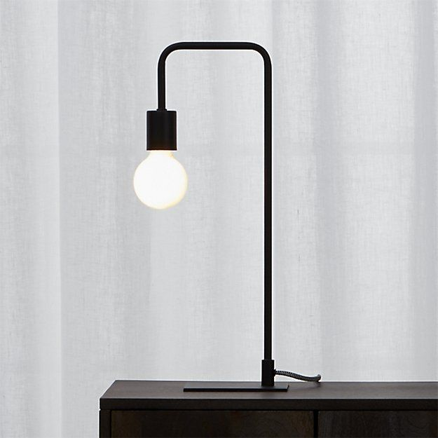 light circuit. Brilliant in its minimalist form, textured black lamp suspends an exposed bulb in one sleek swoop. Two-tone cloth cord adds fresh contrast. We see it glowing bedside, on a bookshelf or on either end of a credenza.