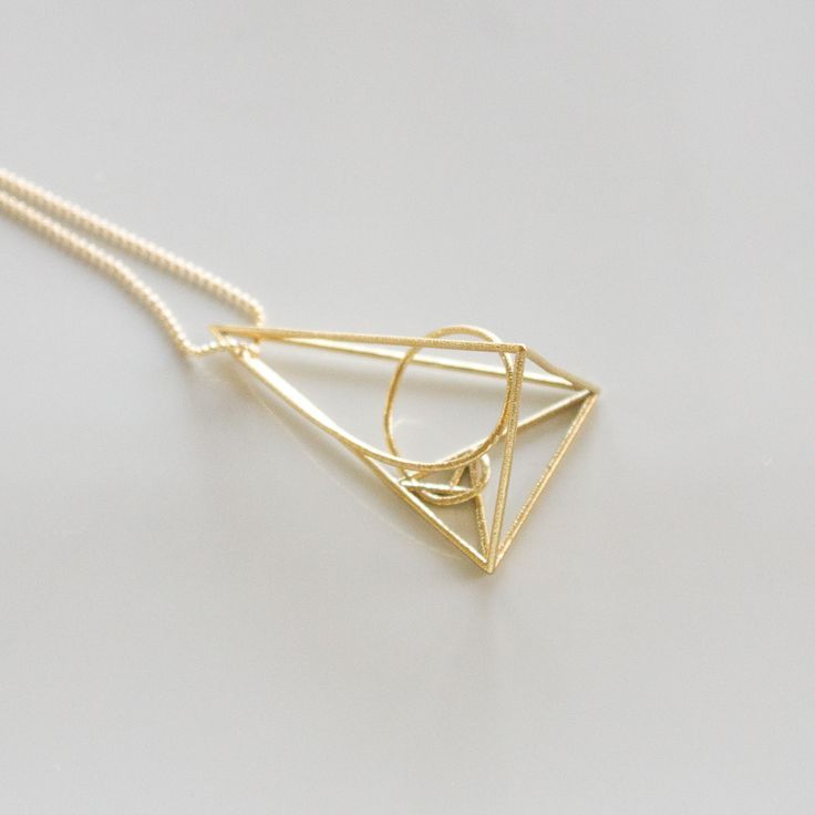 This triangular golden ratio necklace presents the math within nature, beauty within life. The necklace comes with a matching chain. Dimensions: 26x24x41 mm In-stock item will be shipped next day.