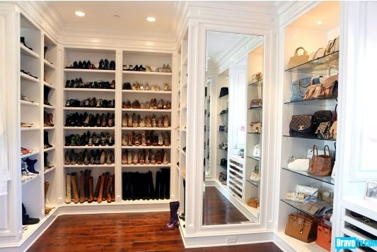 Yolanda Foster's Closet - Amazing walk-in closet design with floor to ceiling shelves for shoes and boots. Dream closet with built-in wall mirror and built-in nook with glass shelves to display designer handbags.