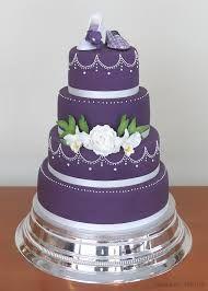 lila bröllopstårta -Vaniljbottnar fyllda med hallonmousse och rårörda hallon samt glasscreme, spacklade med vaniljsmörkräm och täckta med marsipan.