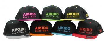 Snapback Cap - Aikido live it - feel it   Bedrucktes 5 Panel Snapback Cap. Schwarzes Cap mit farbigem Schirm und farbigen Luftlöchern. Der Text ist ebenfalls farblich abgesetzt.  - Material: 100 % Baumwolle (Twill) - Kontrastfarbener Schirm, Luftösen und Knopf - Plastik-Klipp-Verschluss im Retro-Look - Einheitsgröße
