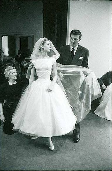 See shots of Audrey Hepburn being fitted for her 'Funny Face' wedding dress by Hubert de Givenchy.