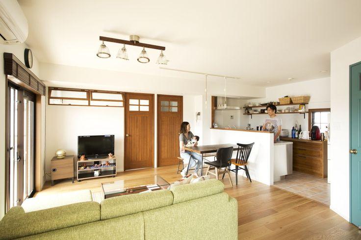 リビングダイニングは、洋室の壁をなくして大空間に。キッチンも一体にしました。 居室の間には室内窓を造作し、明るさや伸びやかさ、風通しを高めています。 室内窓と建具の高さを揃え、木枠は同じ色で塗装するなど、木のぬくもりが落ち着きを醸し出す住まいが誕生しました。 リビングダイニングの床材にはオークのフローリングを採用。 既成の窓枠やウッドブラインド、建具、キッチンの背面収納など、要所でダークブラウンが多く使われていたので、明るい色の樹種を選んでバランス良く仕上げた。