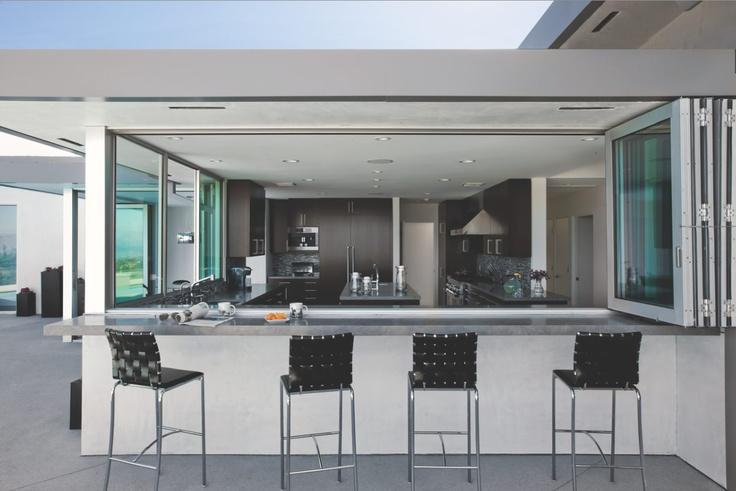 Bi-fold windows slide open to incorporate the outdoor bar seating into the kitchen. Mid-century modern, sliding glass, modern kitchen, dark cabinets, http://www.westernwindowsystems.com