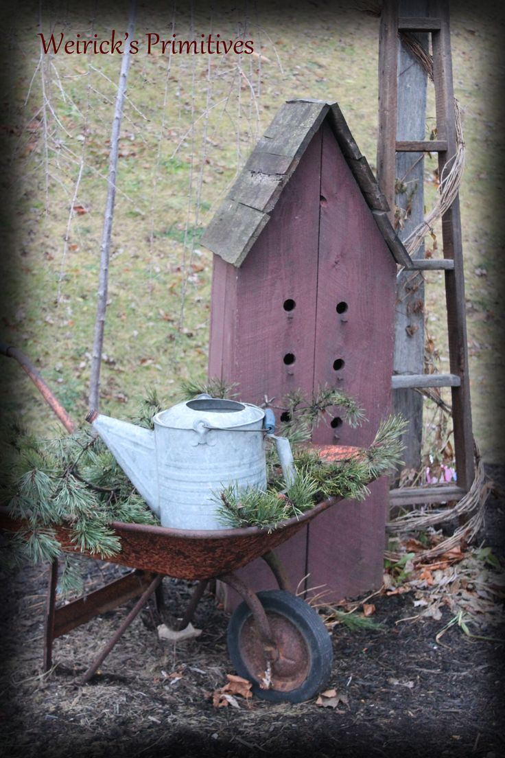 Christmas at the Weirick's........our outdoor decor....old birdhouses. antiques. old watering cans. greens. primitives. decor https://www.facebook.com/pages/Weiricks-Primitives/182707055133836