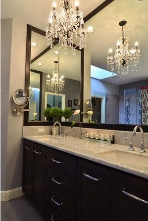 Glamourous bathroom with Chandelier. All in black and white and complemented by the large mirrors on more than one of the walls. Great interior design!