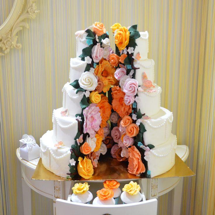 Despicat in cele doua jumatati, este printre cele mai inedite modele de torturi de nunta. Cele doua jumatati egale sunt completate de o multime de flori colorate, toate realizate manual petala cu petala. Indrazneste sa ai parte de un tort spectaculos la nunta ta.  Pret 2400 lei (15 kg).