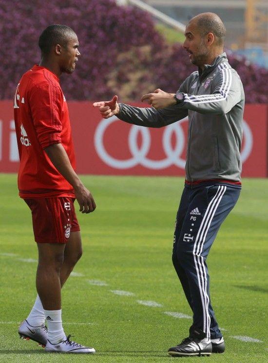 O técnico Guardiola instrui Douglas Costa em treino do Bayern (Karin Jaafar - 10.jan.2016/AFP)