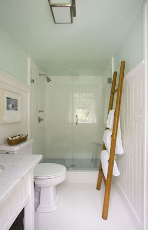Love this white green blue cottage beachy bathroom design with green blue walls paint color, glossy white beadboard, bamboo ladder towel holder and white bathroom sink vanity with white carrara marble countertops.