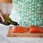 Drizzle some oil over the top of each salmon — just enough to coat the salmon — and rub it over the salmon with your fingers or a pastry brush.