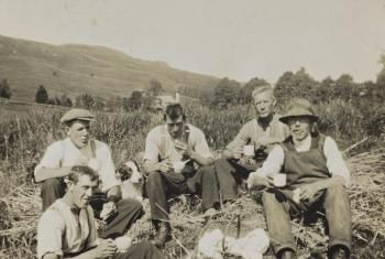 This is a digital copy of black and white photograph of men, including Robert McMillan (left) and Hugh McMillian (centre), cutting the corn with scythes at Shankfoot Farm, Moniaive, Dumfriesshire in the 1950s.