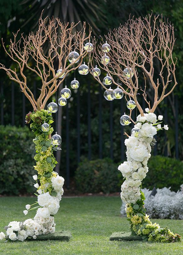 Branches create an archway with lovely white & green flower arrangements and hanging glass bubbles. Wedding Ceremony Decoration