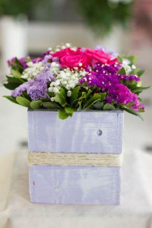 Σύνθεση λουλουδιών με τριαντάφυλλα και αμάραντο σε ξύλινο κασπώ.