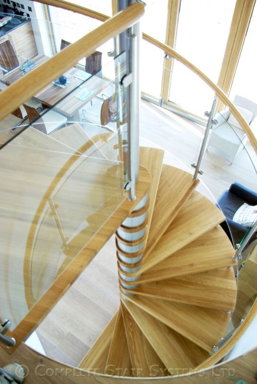 Spiral stair with curved glass infill panels and oak treads