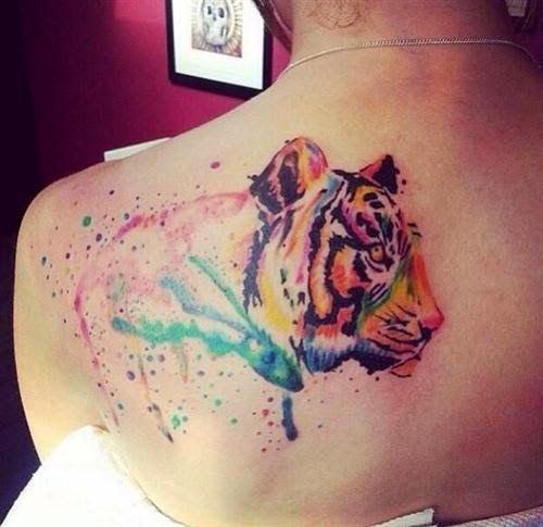 Joli tigre aquarelle tatoué sur l'épaule https://tattoo.egrafla.fr/2016/02/12/modeles-tatouage-aquarelle/