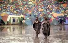 Glastonbury in raincoats! Two festival-goers enjoy a pizza at the mud and rain drenched Glastonbury festival, 1998