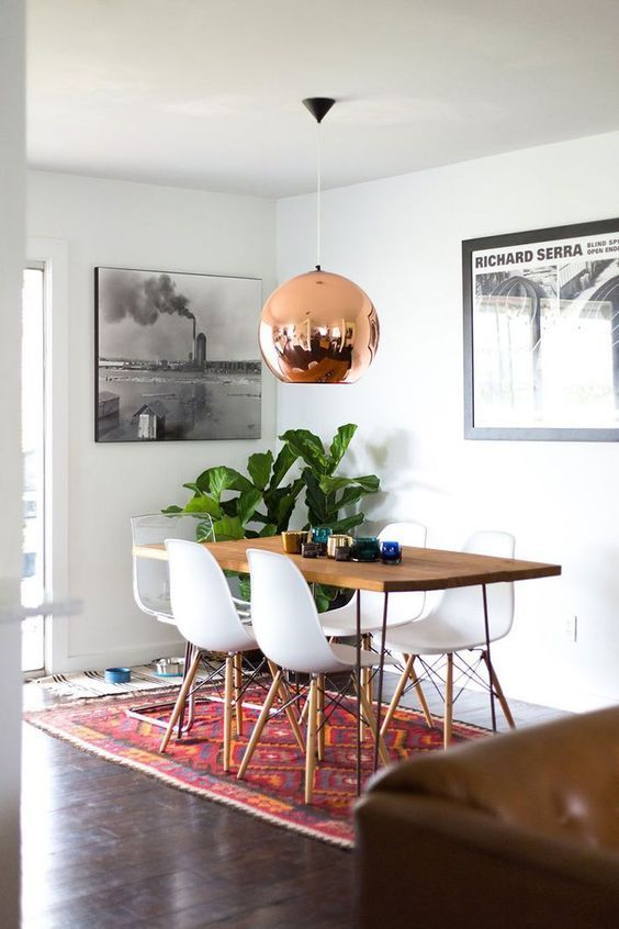 A modern dining room design featuring large black and white artwork, a contemporary copper hanging pendant light, a wood top table with metal legs, white Eames chairs, and a colorful woven area rug - Home Decor & Decorating Ideas