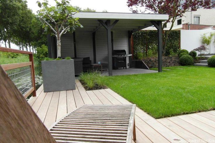 Heerlijk buitenleven, tuin te 's-Gravendeel modern-tuinontwerp-gras-gazn-overkapping-buitenverblijf-hillhout-grijs-antraciet-vlonder-die-niet-glad-wordt-garappa-houten-vlonder-vijg-in-bak-klein-boompje-in-bloembak-loungeset