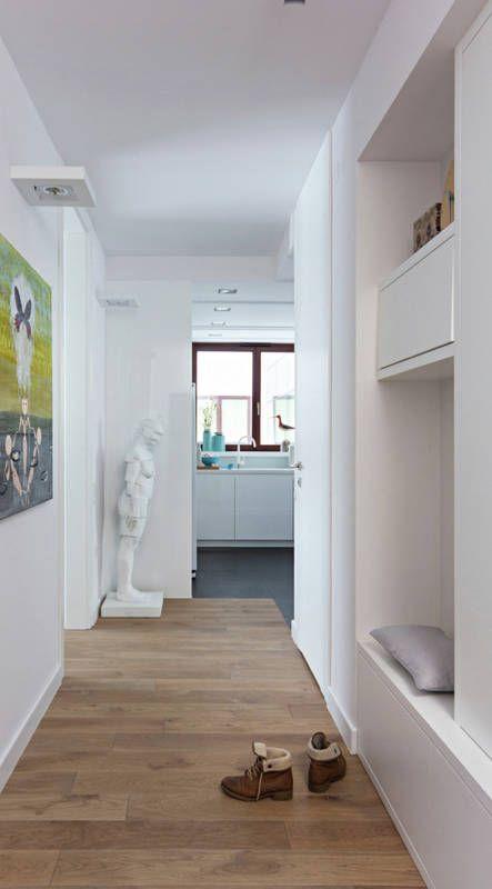 W tym przedpokoju szafę na okrycia wierzchnie oraz szafki na buty ukryto w jasnej zabudowie, z garderobą na końcu. Na uwagę zasługuje funkcjonalne siedzisko do zmiany obuwia.